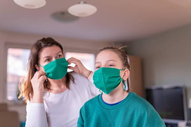 Mutter und ihre Tochter tragen eine grüne hausgemachte Schutzmaske zu Hause – Foto