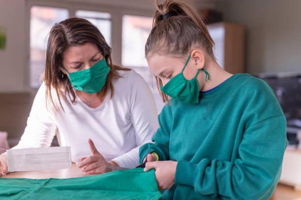 Mutter und ihre Tochter tragen und erstellen grüne hausgemachte Schutz Gesichtsmaske zu Hause – Foto