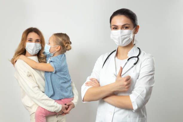 Mother and her daughter wearing medical masks in hospital stock photo