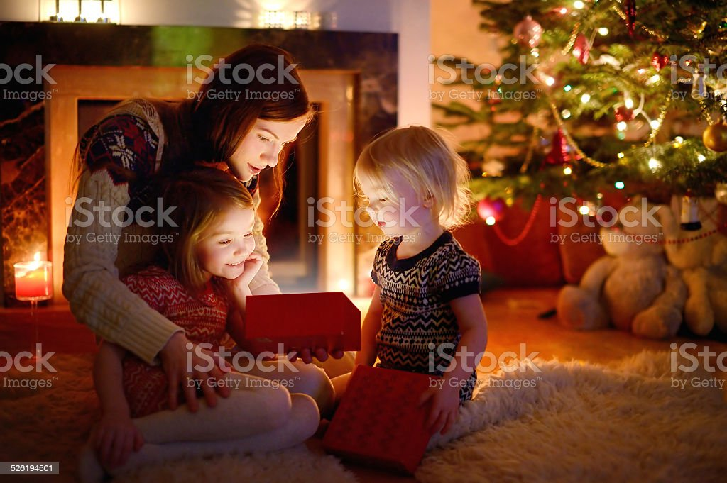 Mother and her daughters opening a Christmas gift stock photo