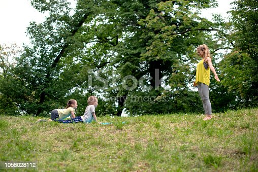 466808392 istock photo Mother and her kids doing yoga 1058028112
