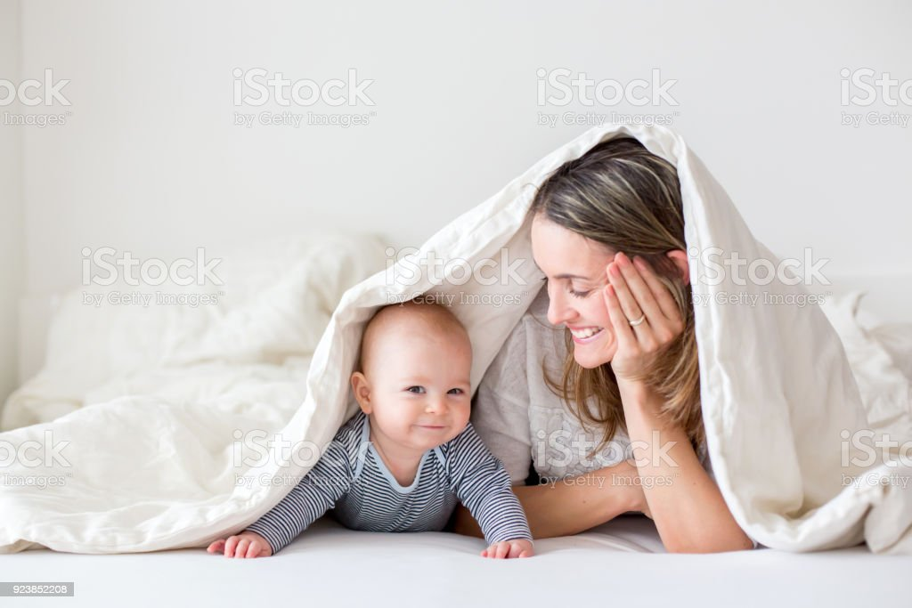 Mother and her little baby boy, playing together in bedrroom stock photo