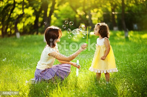 507271044istockphoto Mother and her little daughter playing with bubbles 530631297