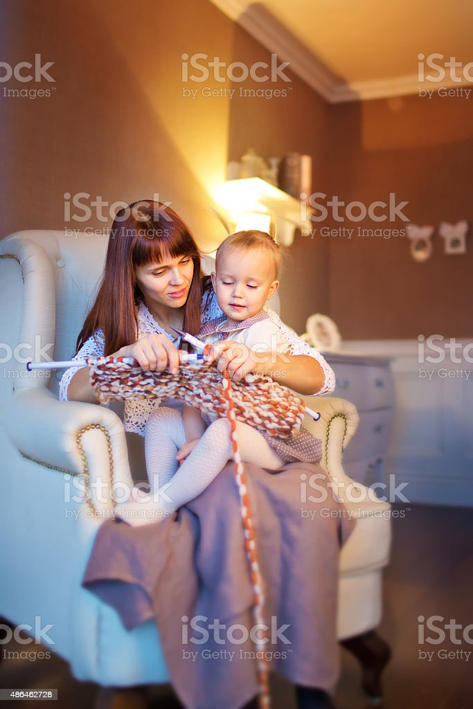 Mother and her little girl are knitting stock photo
