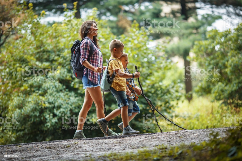 Mother and her little sons hiking trough forest by the road . stock photo