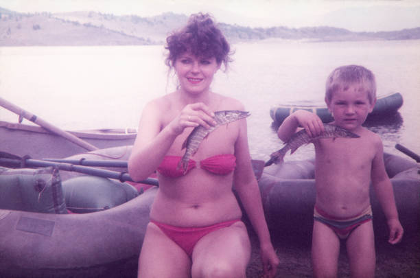 Mother and her son fishing pikes on lake. stock photo