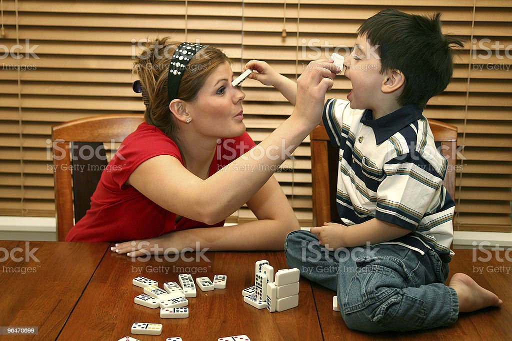 A mother and her son playing dominoes royalty-free stock photo