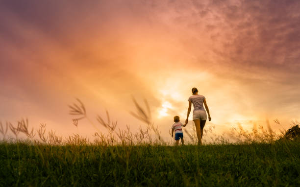 Mother and her son walking at sunset stock photo