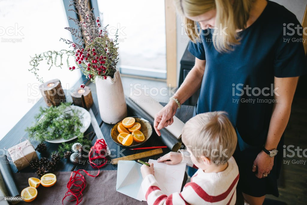 Mother And Her Son Writing A Letter Ta Santa Claus Stock Photo