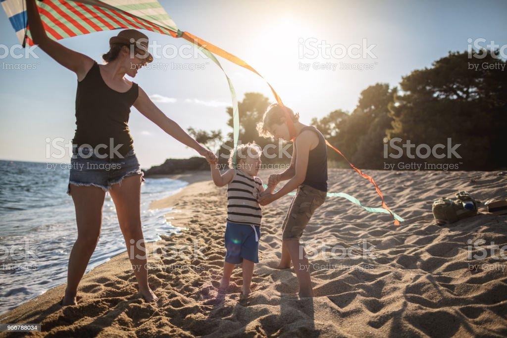 Mutter mit ihren Söhnen einen Drachen am Strand – Foto