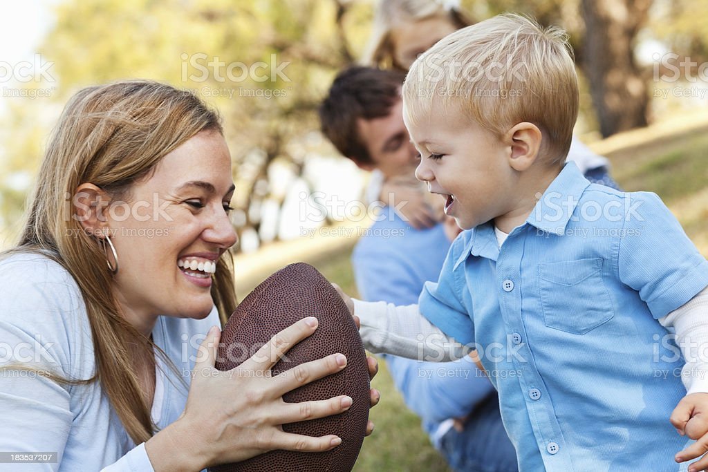 Mother and Her Young Son Playing With Football at Park stock photo