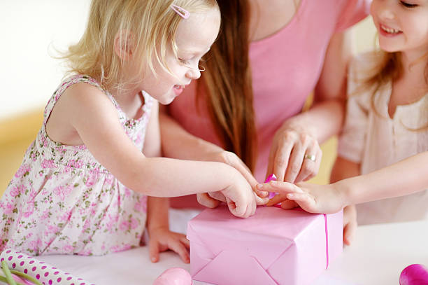 Mother and het two daughters wrapping a gift Young mother and her two little daughters wrapping a gift with pink wrapping paper birthday wishes for daughter stock pictures, royalty-free photos & images