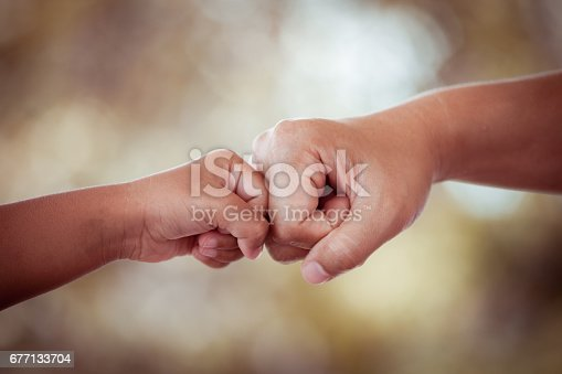 istock mother and kid daughter are fist bumping in vintage color tone 677133704