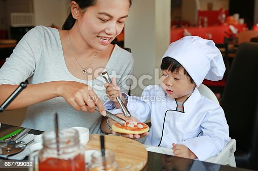 istock Mother and Kid girl in a suit of the little chef make mini pizza. 667799032