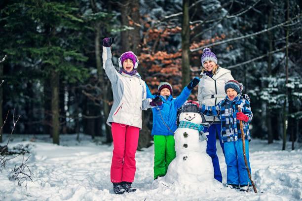 mutter und kinder einen schneemann bauen, wintertag - schneemann bauen stock-fotos und bilder