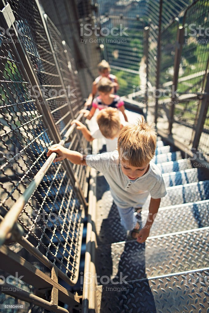 Mother and kids climbing stairs of Eiffel Tower stock photo