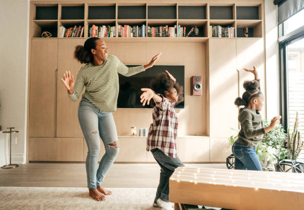 Mother and kids dancing Winter family fun dancing stock pictures, royalty-free photos & images