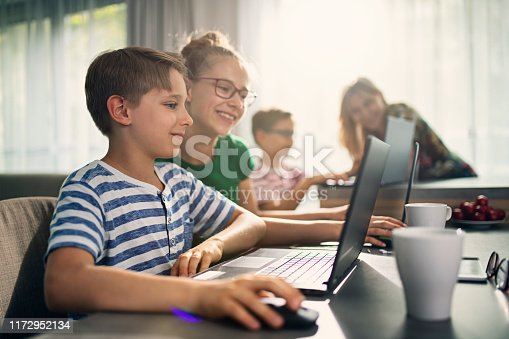 istock Mother and kids doing homework at home 1172952134
