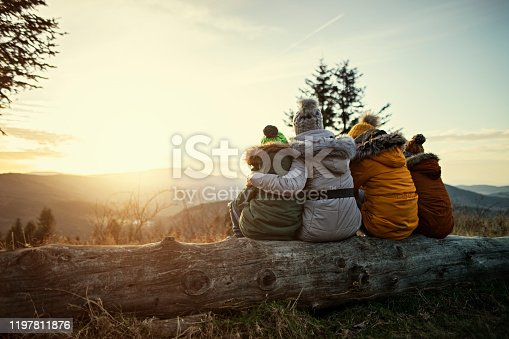 Mother and three kids hiking in mountains. Family is sitting on tree trunk and looking at sunset and view. Cold winter or autumn day. Nikon D850