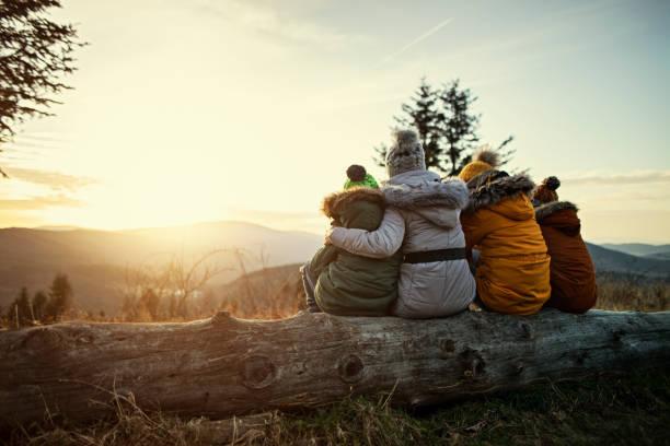 madre y niños disfrutando de la puesta de sol en las montañas - invierno fotografías e imágenes de stock