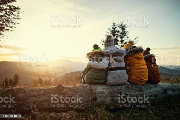 Photo of Mother and kids enjoying sunset in mountains