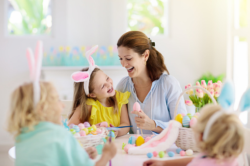 Mother and kids color Easter eggs. Mom, little girl and boy with bunny ears dying and painting for Easter egg hunt in white sunny room. Family celebration and home decoration for spring holiday.