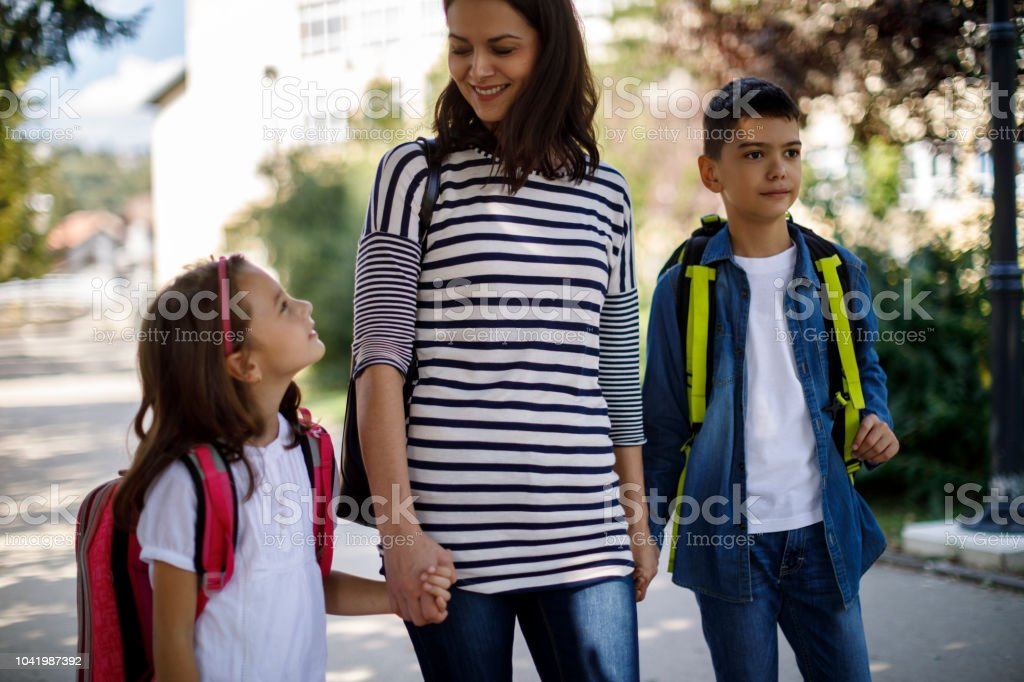 Mother and kids going home from school