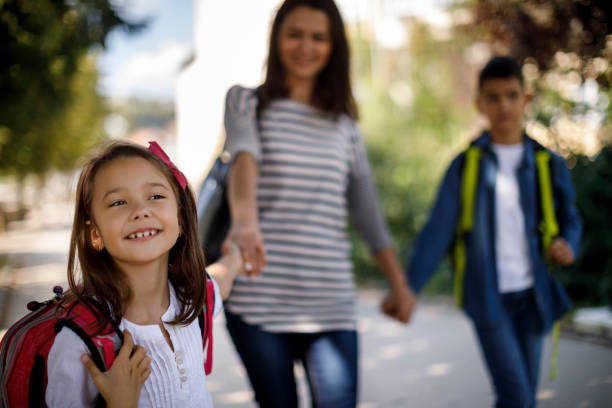Mother and kids going home from school stock photo