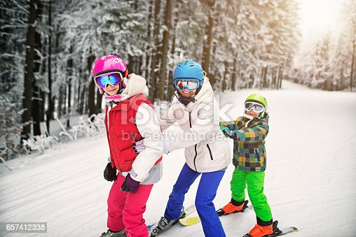 istock Mother and kids having fun skiing together on winter day 657412338