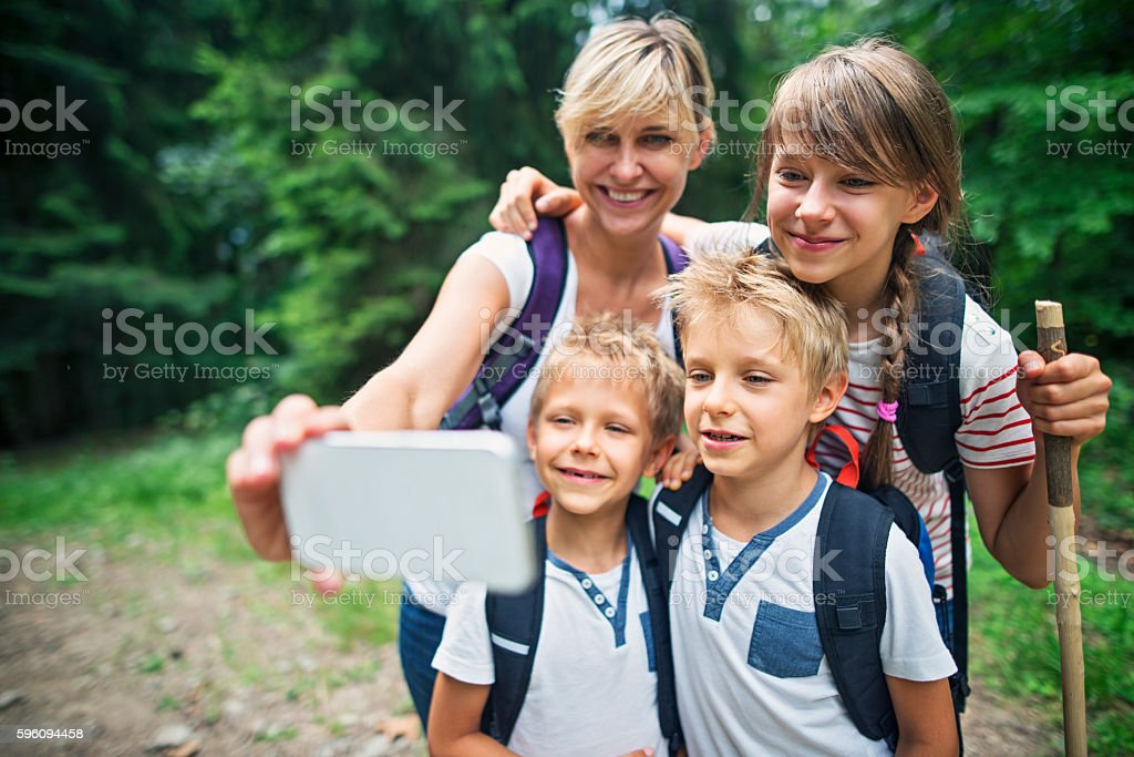 Mother and kids hikers taking selfie in forest Lizenzfreies stock-foto