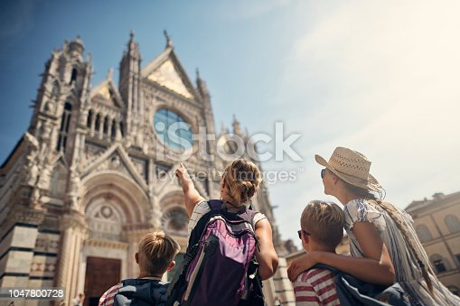 Mother and kids tourists sightseeing beautiful Italian city of Siena. The family is standing in Piazza del Duomo and admiring the facade of the famous Siena Cathedral. Nikon D850