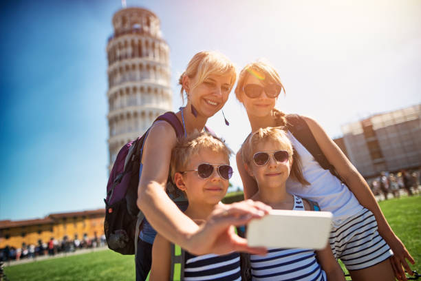 Mother and kids taking selfie in Pisa Mother and kids visiting Pisa, Italy. The family is taking selfie in the Piazza del Miracoli. The famous leaning tower of Pisa is visible in the background. The family is smiling at the mobile phone.    pisa stock pictures, royalty-free photos & images