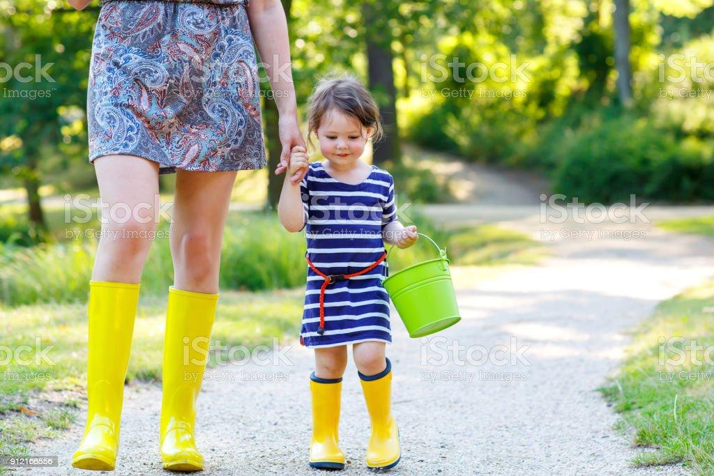 Mutter und wenig liebenswert Kleinkind Kind in gelben Gummistiefeln, Familie Look im Sommerpark. Schöne Frau und niedliche Mädchen Tochter zusammen spazieren – Foto
