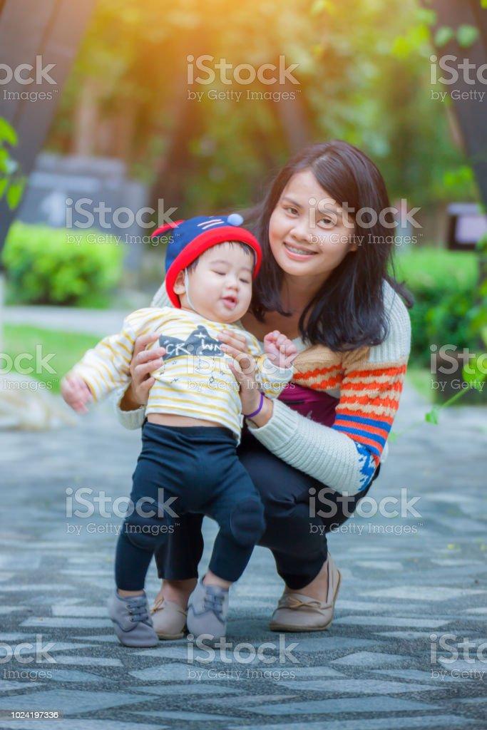 Mutter und kleine asiatische Baby Boy in Santa Claus Hut und Blick in die Kamera, die gute Zeit im Freien auf den Naturpark. Konzept der freundliche Familie und der Sommerurlaub – Foto