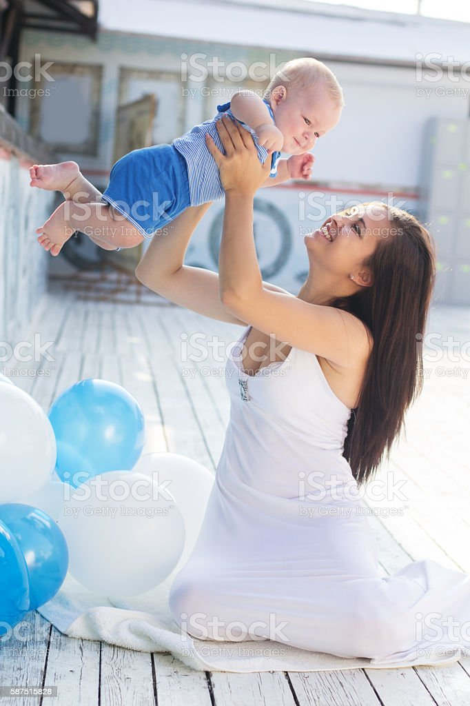 Mother and little baby boy with balloons outdoors stock photo