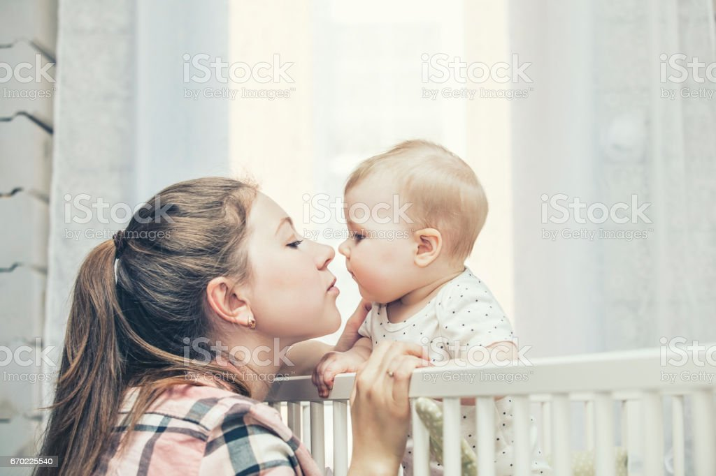 Mother and little baby is in the crib woke up in the morning and smiling stock photo