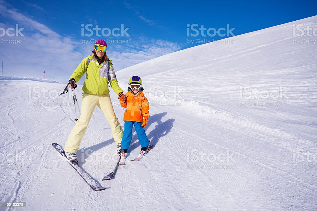 Mother and little boy learning to ski holding hand stock photo