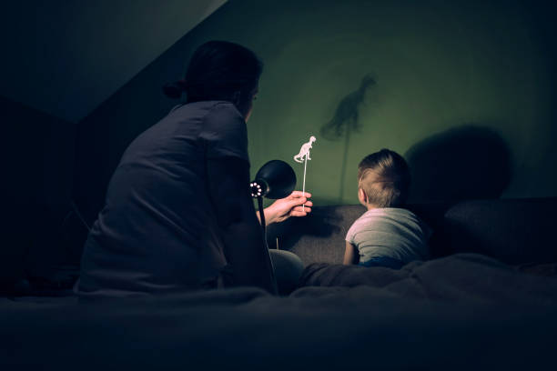 Mother and little boy playing with shadows Mother and little boy playing with dinosaur shadows storytelling stock pictures, royalty-free photos & images