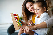 istock Mother and little cute girl, kid playing with abacus, early education 1248950898