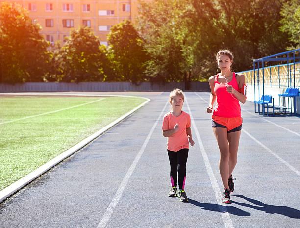 mother and little daughter are doing exercise in the stadium - kinder die schnell arbeiten stock-fotos und bilder