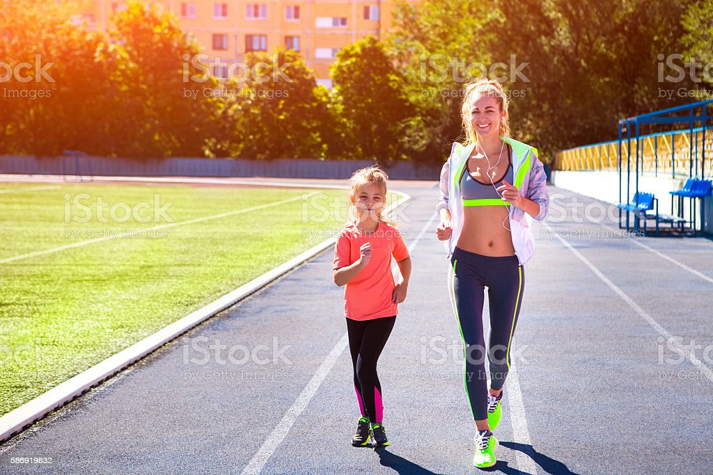 Mother and little daughter are doing exercise in the stadium stock photo