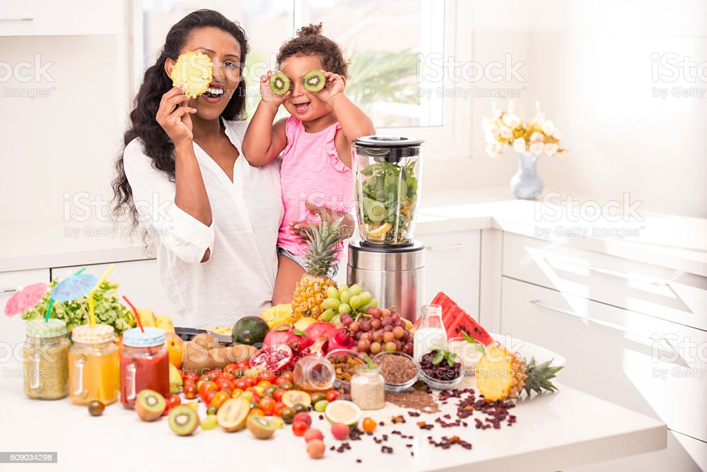 Mother and little daughter blending fruits. stock photo
