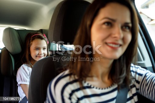 Mother and little daughter driving in car together