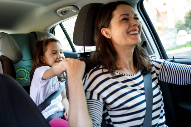 Mother and little daughter driving in the car together stock photo
