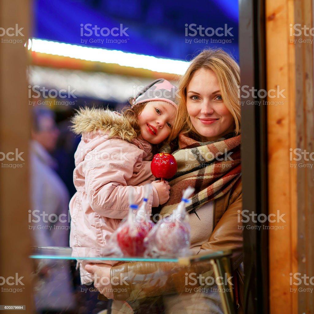 Małe matka i córka jedzenia Jabłko crystalized na święta zbiór zdjęć royalty-free