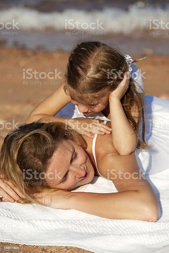 Mother and little daughter having fun on beach royalty-free stock photo