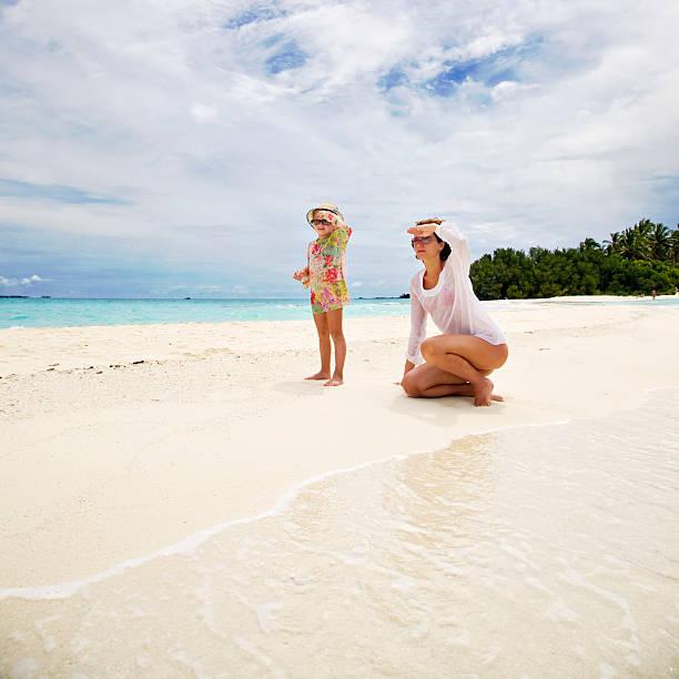 Mutter mit kleinen Tochter am tropischen Strand – Foto
