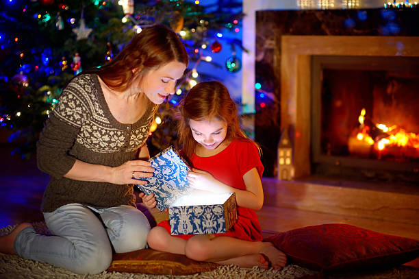 mother and little daughter opening a magical christmas gift - little girls giving head stock photos and pictures