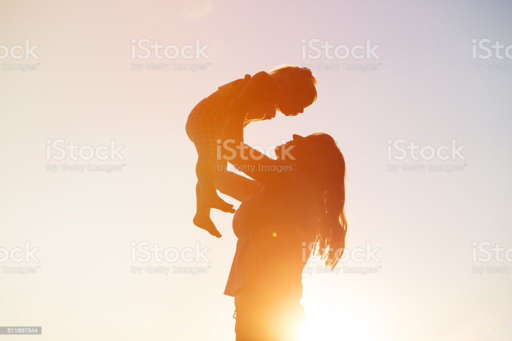 mother and little daughter play at sunset stock photo