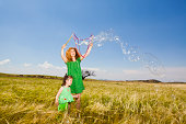 Mother and daughter creating giant soap bubbles in yellow field